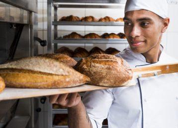 panadero-macho-joven-sacando-pala-madera-pan-recien-horneado-horno_23-2148189052