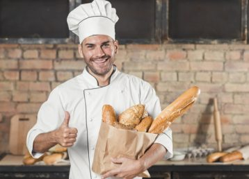 panadero-sexo-masculino-joven-sonriente-que-sostiene-pan-panes-bolsa-papel-que-muestra-pulgar-encima-muestra_23-2147883313