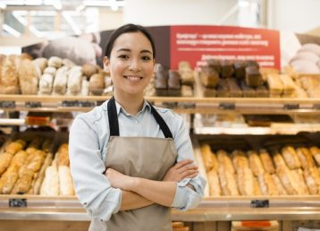 vendedor-femenino-asiatico-alegre-panaderia-brazos-cruzados-supermercado_23-2148216125